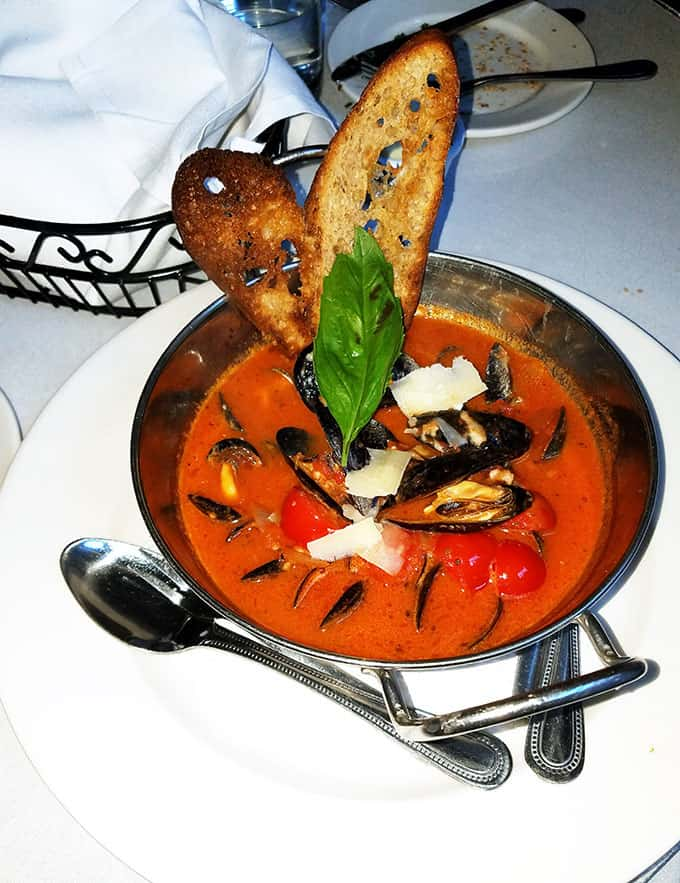 Mussels in Tomato Sauce with two pieces of toasted bread in a bowl from Irene\'s Cuisine in New Orleans