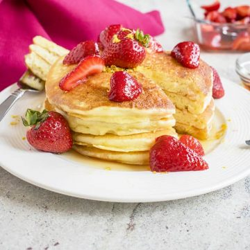stack of Lemon Ricotta Pancakes with strawberries on a plate