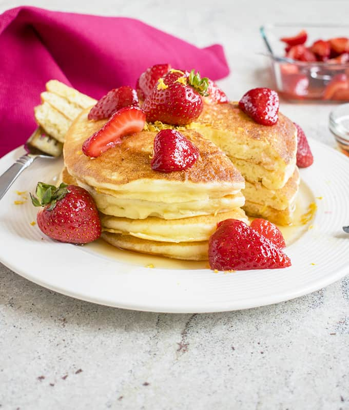 Photo of stack of Lemon Ricotta Pancakes with strawberries on a plate