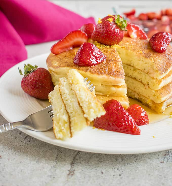 Photo of stack of Lemon Ricotta Pancakes with strawberries and a forkful of pancakes