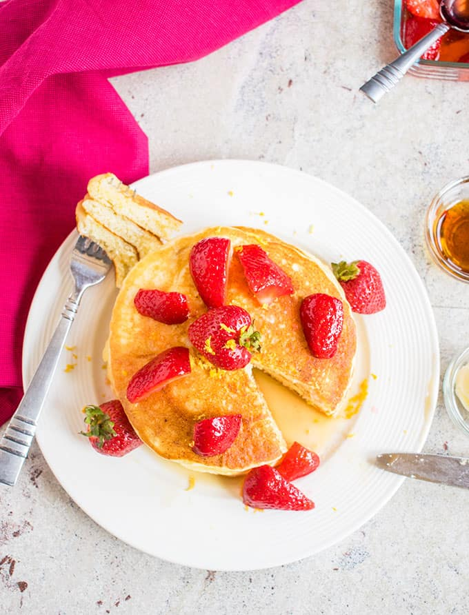 Overhead picture of Lemon Ricotta Pancakes topped with strawberries with a forkful to the side