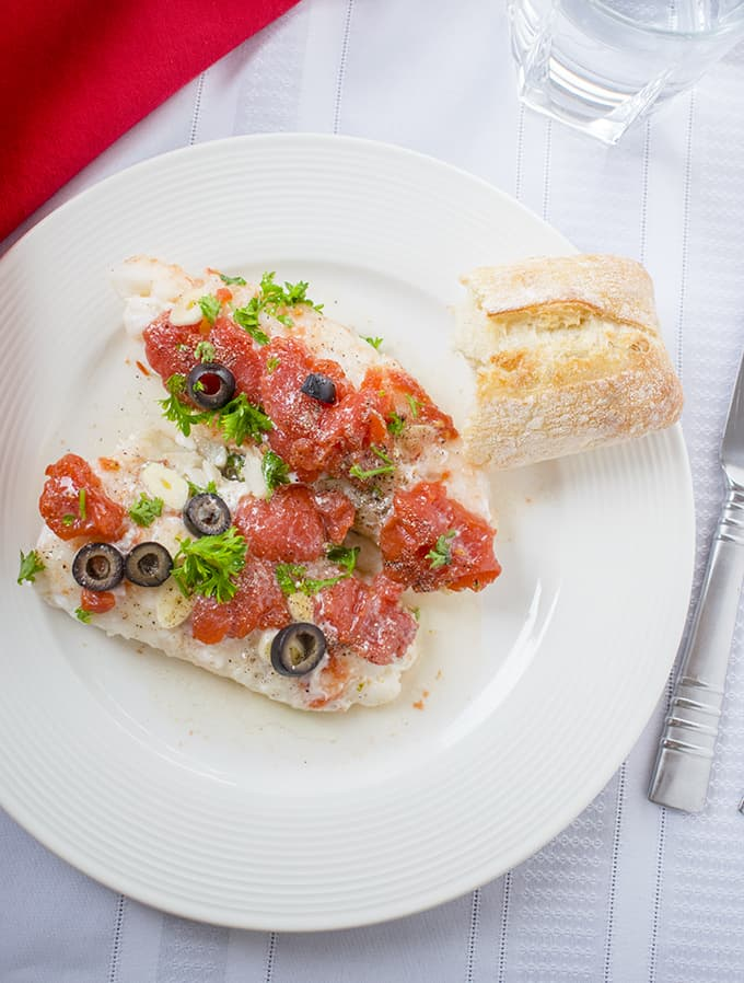 Photo of Sauteed Cod with Tomatoes in a Plate with Bread
