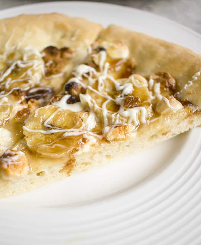Closeup photo of slice of dessert pizza with bananas and white chocolate