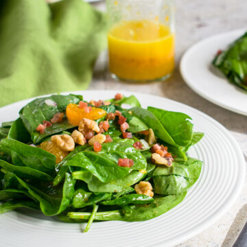 spinach salad topped with mandarin oranges and pancetta on a plate and a bottle of orange vinaigrette