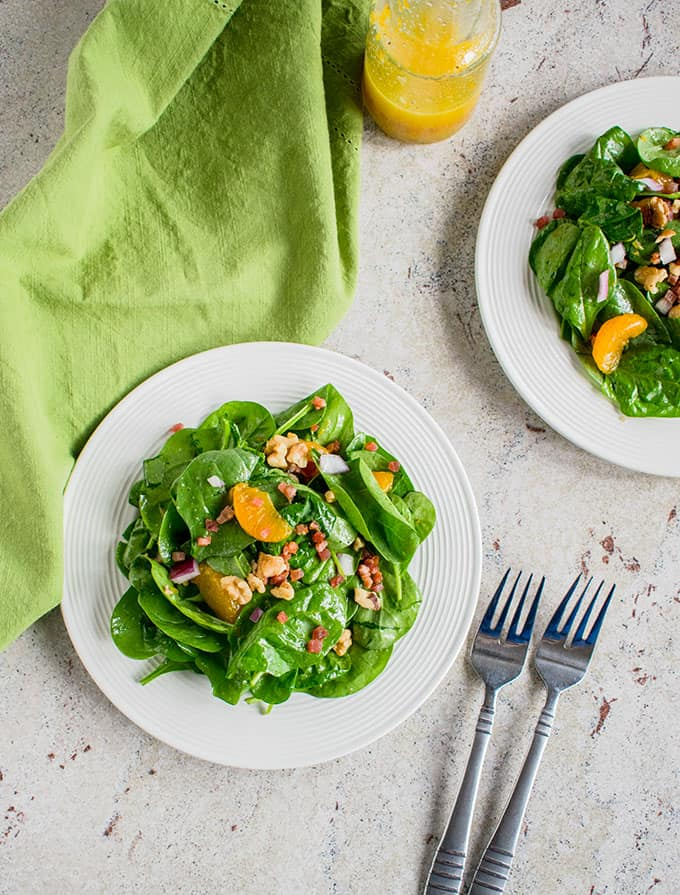 Overhead photo of two plates of Spinach Salad with Mandarin Oranges and Pancetta with two forks and green napkin