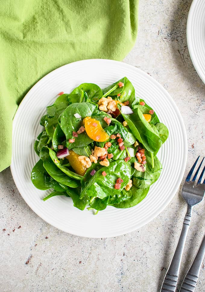 Plate of spinach salad with mandarin oranges and pancetta beside a fork and napkin