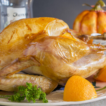 Whole Thanksgiving turkey on a platter with greens and an orange slice
