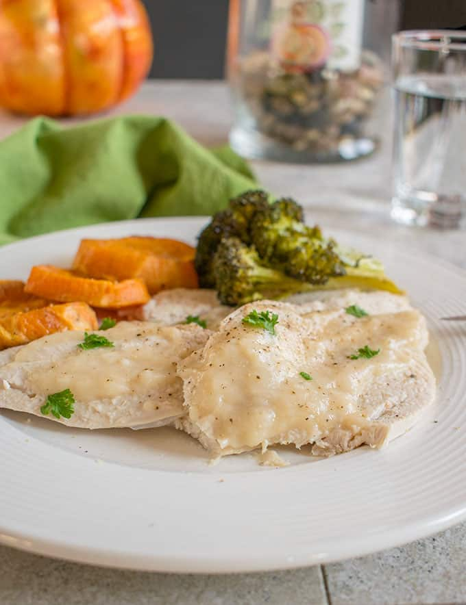 Photo of plate of sliced Thanksgiving turkey with gravy, sweet potatoes and broccoli