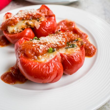 Photo of plate of two Italian stuffed pepper halves with sauce and cheese