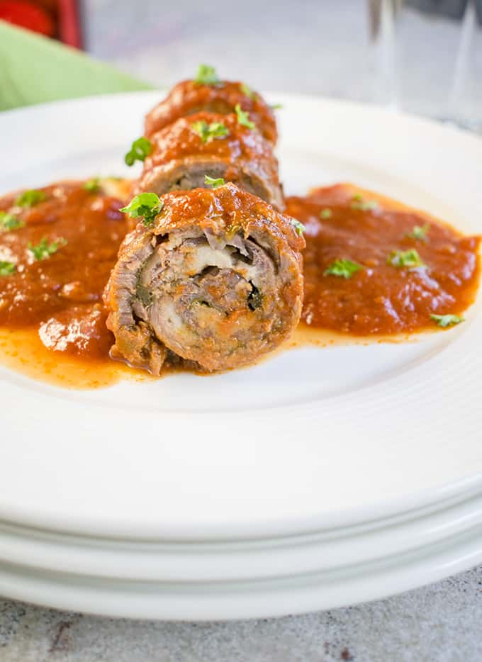 Closeup photo of sliced braciole on plate with sauce