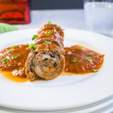 Photo of sliced braciole on plate with tomato sauce