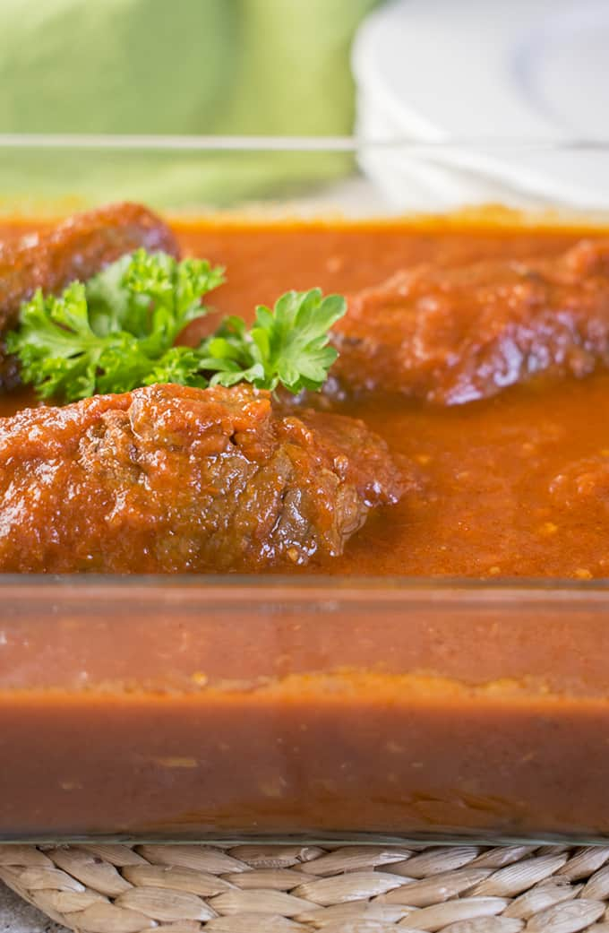 Photo of glass container of sauce with three braciole