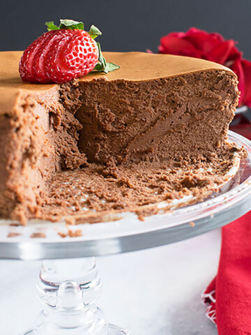 chocolate cheesecake on cake stand with sliced strawberry on top
