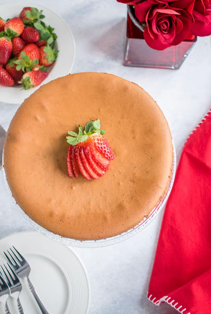 Overhead photo of Chocolate Crustless Cheesecake on cake stand with strawberries and vase of roses