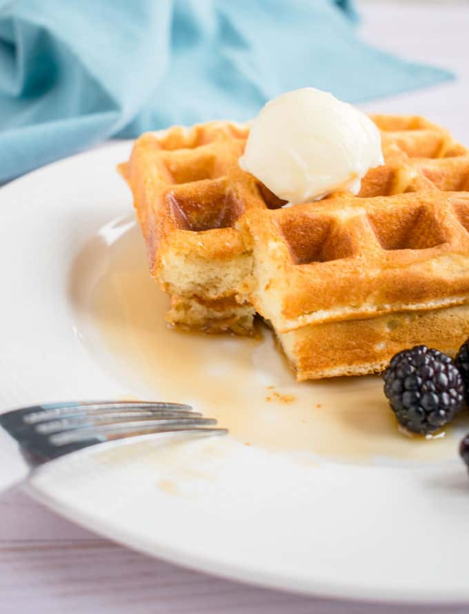 Photo of Homemade Waffles with butter and syrup on a plate with a corner of the waffles missing to show the texture