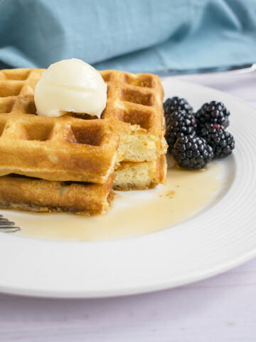 two stacked homemade waffles with butter, syrup and blackberries on a plate