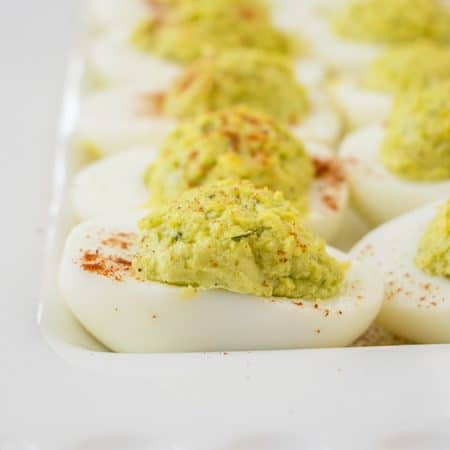 Closeup photo of pesto deviled eggs on a platter