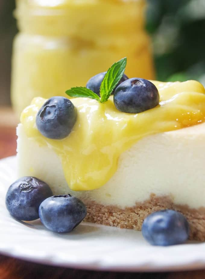 plate of cheesecake topped with lemon curd and blueberries