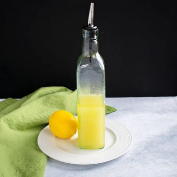 bottle of lemon olive oil on plate with a lemon and green napkin