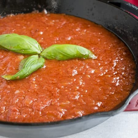pan with marinara sauce and basil leaves
