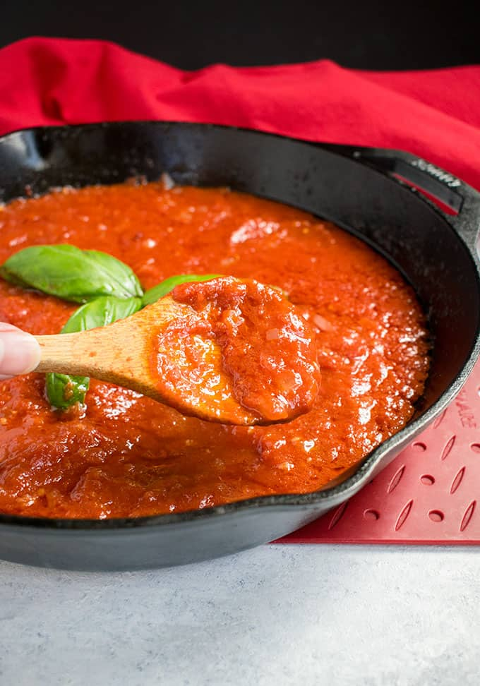 wooden spoonful of marinara sauce from pan