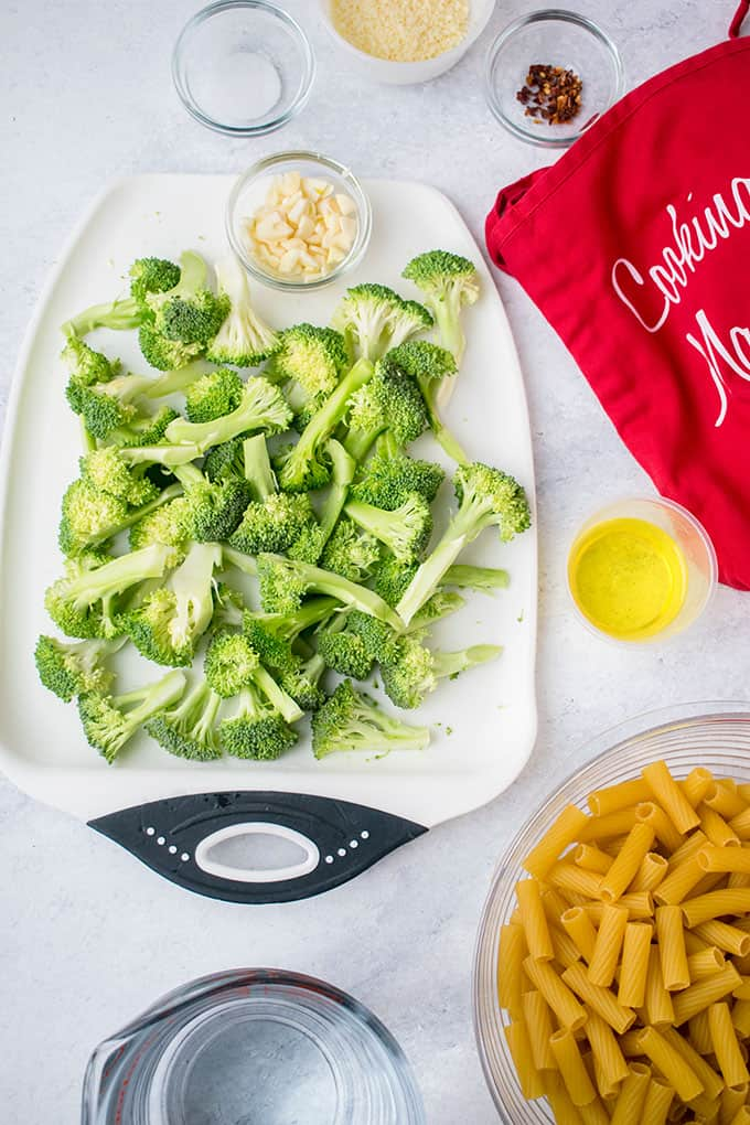 Overhead view of the ingredients for pasta with broccoli ingredients: Pasta, broccoli, olive oil, garlic, red pepper flakes, salt, water and parmesan cheese