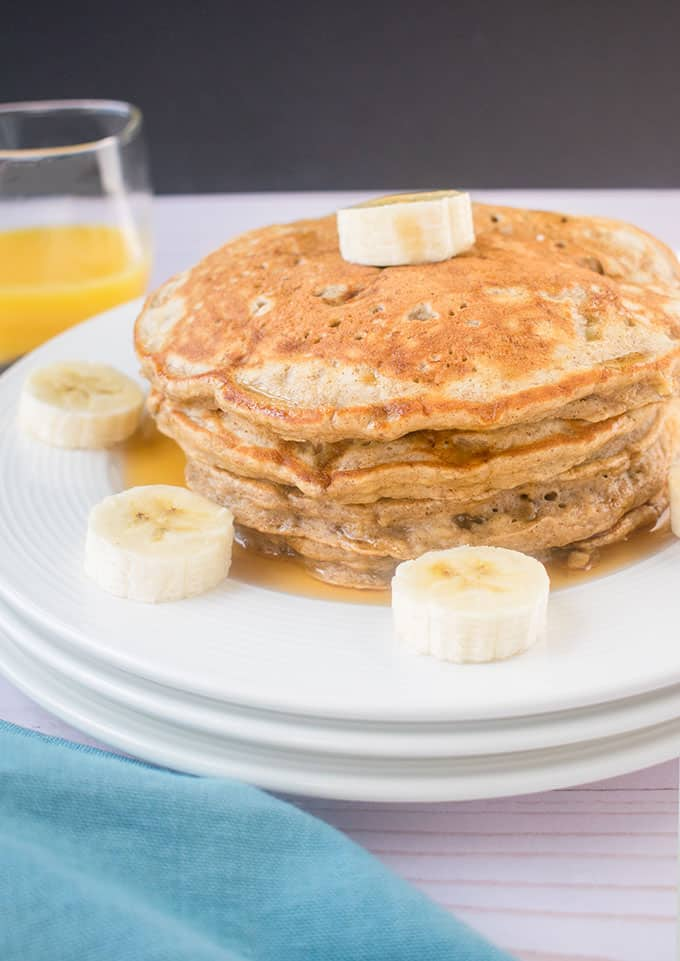 stack of banana pancakes on a plate with banana slices