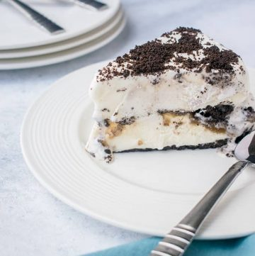 Slice of Oreo Ice Cream Cake on white plate with a spoon