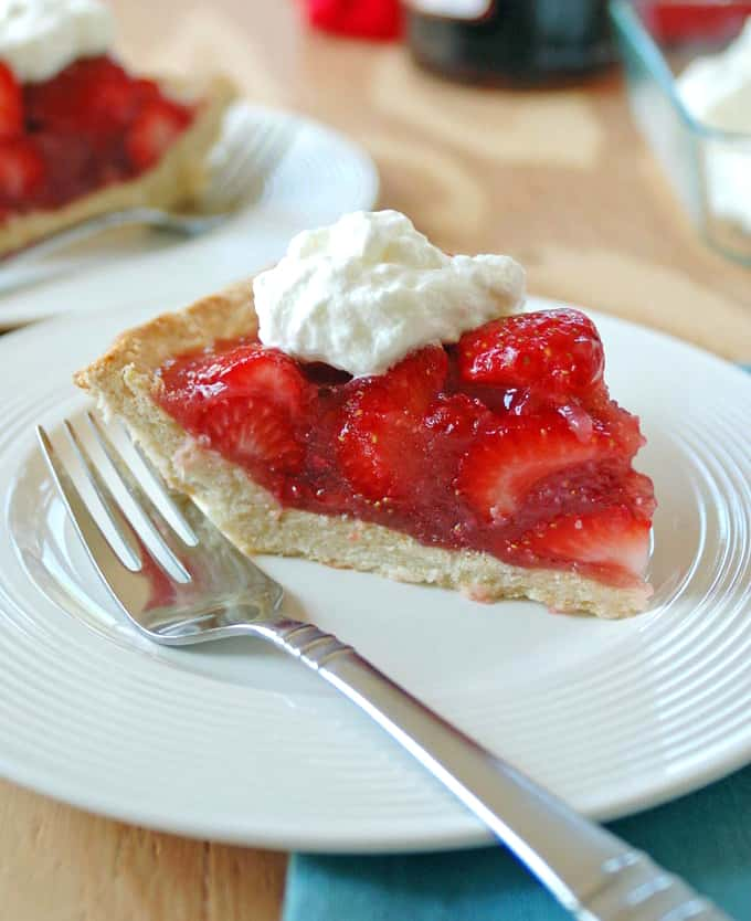 photo of plate with slice of fresh strawberry pie with whiped cream and fork