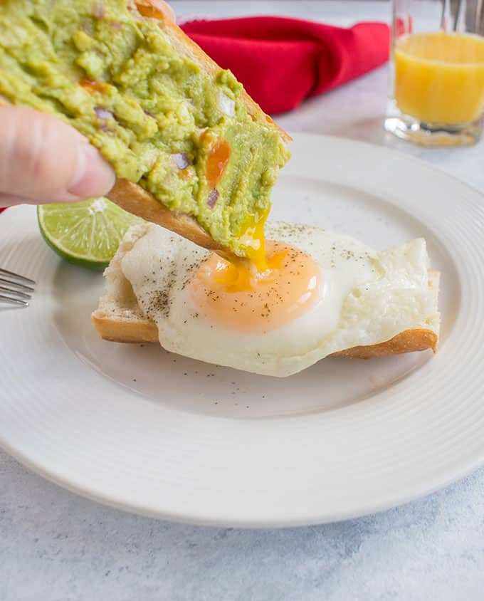 guacamole on toast being dipped into basted egg