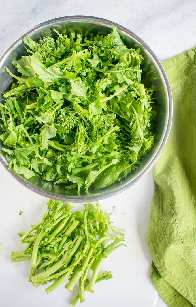 Full bowl of raw rapini with cut stems and a napkin beside it