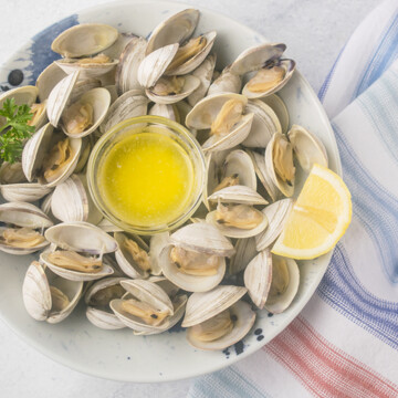 Overhead view of steamed littleneck clams in a bowl with lemon and small dish of melted butter