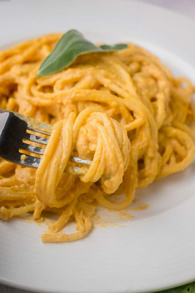 forkful of twirled linguine with creamy pumpkin sauce