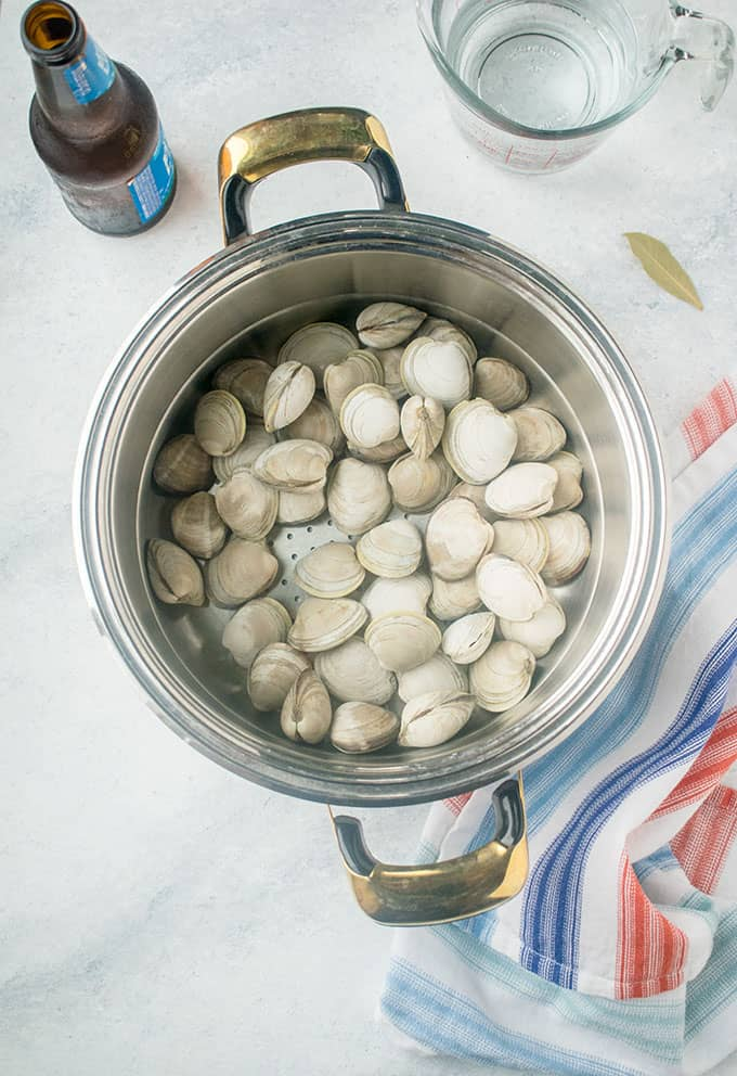 steamer pot with littleneck clams next to beer, bay leaf, napkin