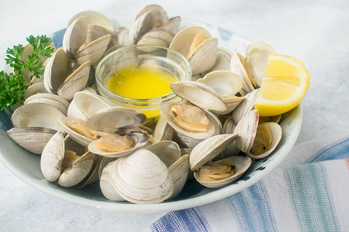 bowl of beer-steamed littleneck clams with melted butter and lemon
