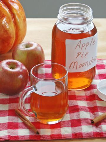 mason jar and glass mug of apple pie moonshine, apples
