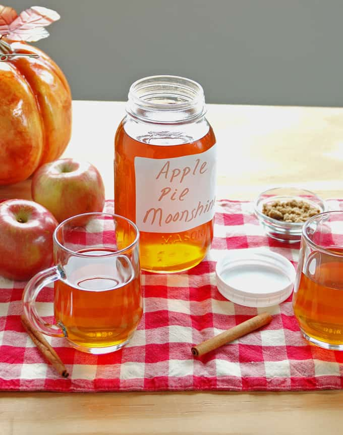 apple pie moonshine in mason jar, glass mugs, apples, cinammon sticks, pumpkins