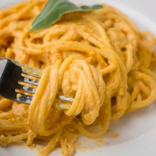 twirled spaghetti with orange sauce on fork, sage leaf