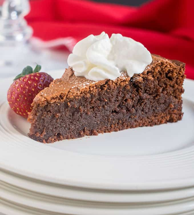 slice of chocolate cake with whipped cream and a strawberry on a stack of white plates, red napkin