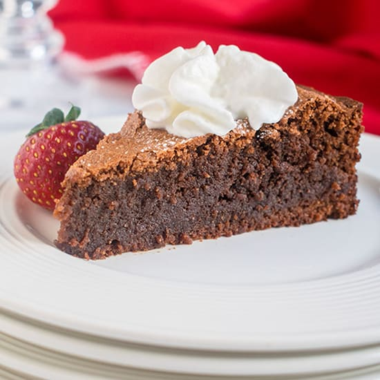 A piece of chocolate cake on a plate with whipped cream and strawberry