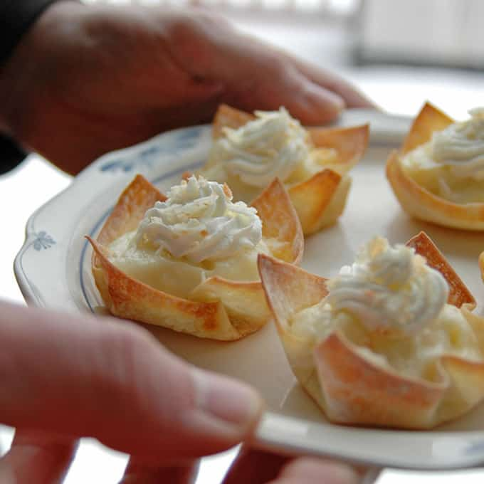 A close up of a person holding a plate of mini pie cups with whipped cream