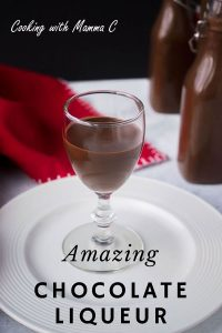 stemmed glass of chocolate liqueur on white plate with red napkin
