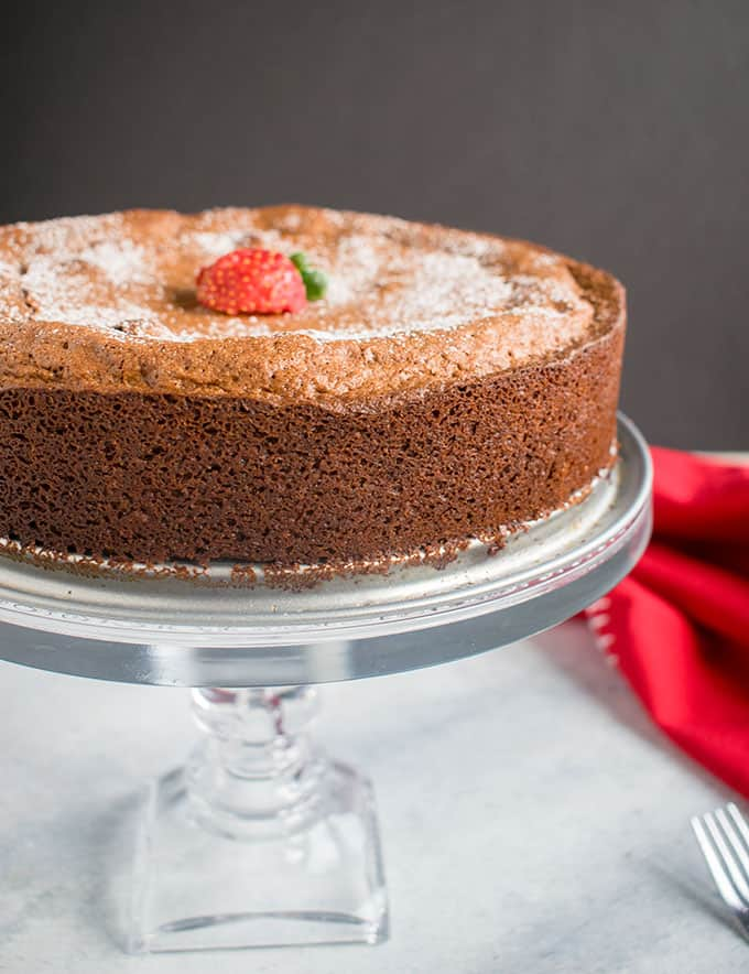 chocolate cake on cake stand with strawberry and powdered sugar on top, red napkin, fork