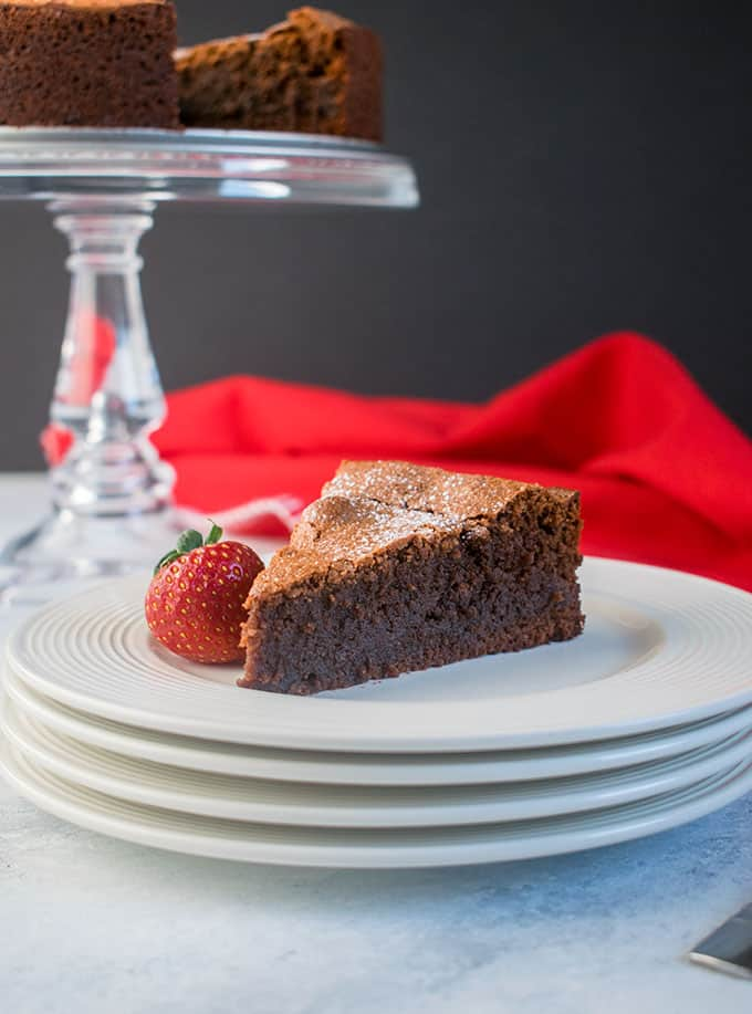 slice of chocolate cake on stack of white plates with strawberry, glass cake stand with chocolate cake, red napkin