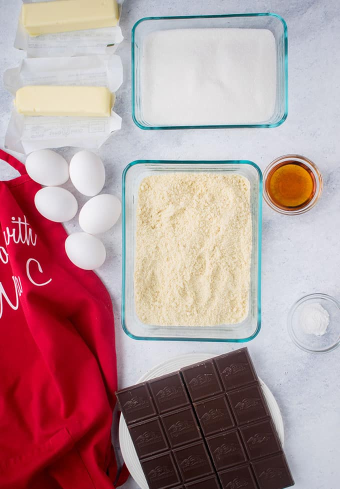almond flour, eggs, sugar, butter, chocolate, vanilla, baking powder, red apron