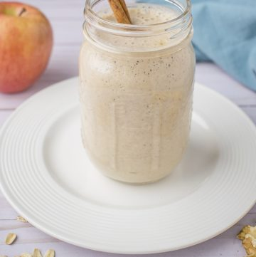 Mason jar with apple smoothie on white plate, red apple, blue napkin