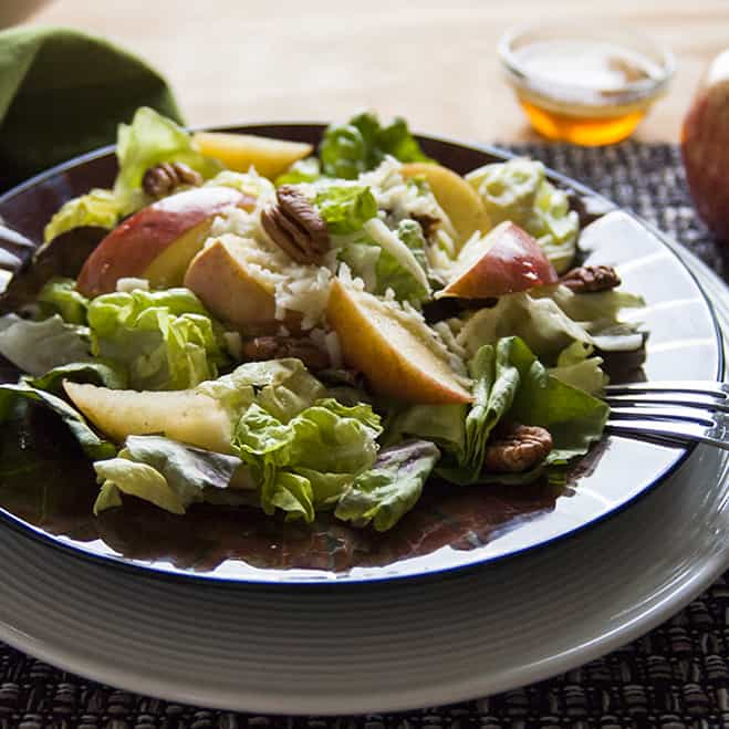 a dish of salad with apple slices, pecans, mozzarella