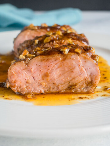 slices of glazed tenderloin on white plate with juices and blue napkin