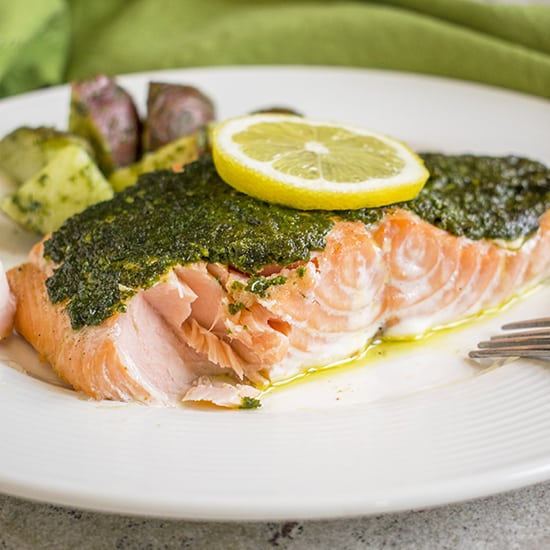 salmon with pesto and lemon slice on plate with potatoes