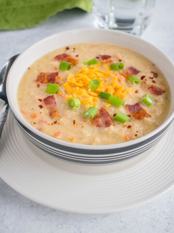 bowl of soup with cheddar, bacon and green onions and spoon
